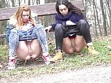 Girls pissing together in park